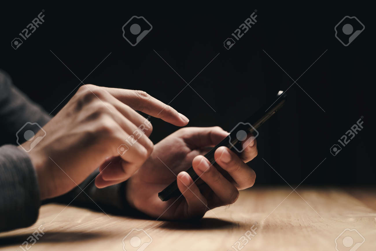 Closeup of a man using a smartphone on the wooden table, searching, browsing, social media, message, email, internet digital marketing, online shopping. - 172185663
