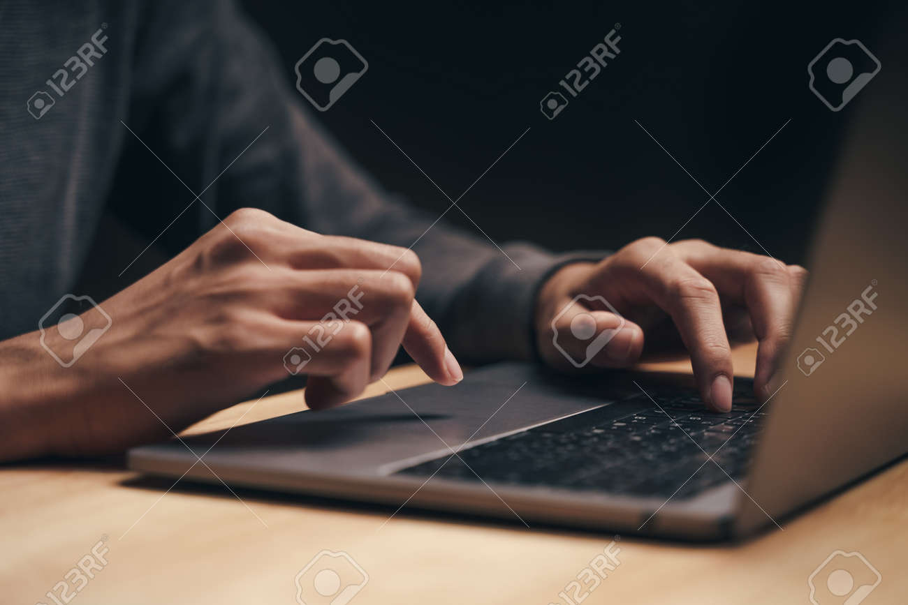 Closeup of a man using a laptop computer on the wooden table, searching, browsing, social media, message, email, internet digital marketing, online shopping. - 172185668