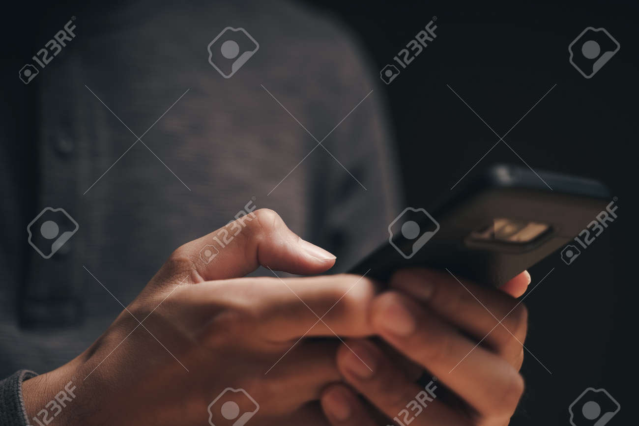 Closeup of a man using a smartphone on the wooden table, searching, browsing, social media, message, email, internet digital marketing, online shopping. - 172185688