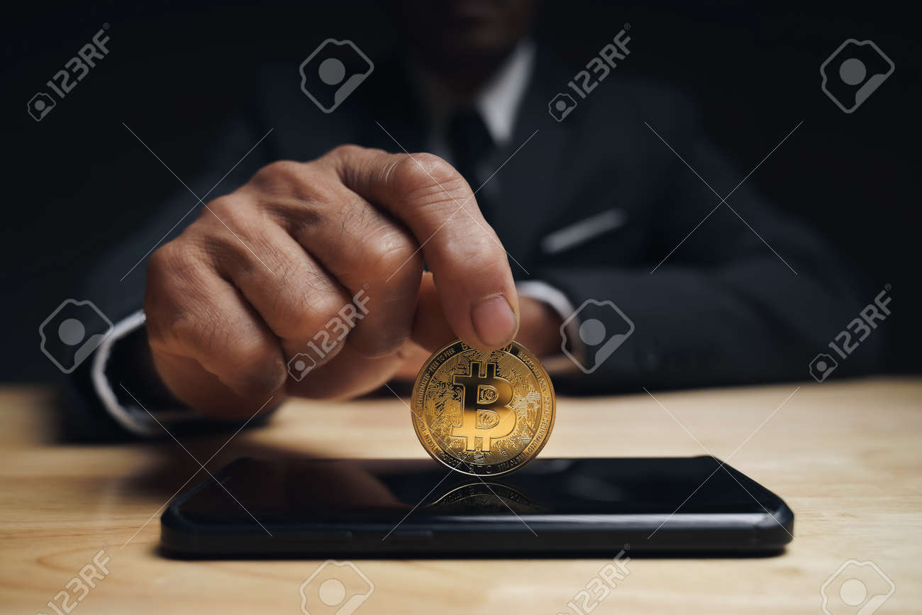 Businessman in black suit holding a golden bitcoin using Smartphone with Bitcoin trading chart on the screen to Trading Cryptocurrency, alternative finance and investment Concept. - 172185694
