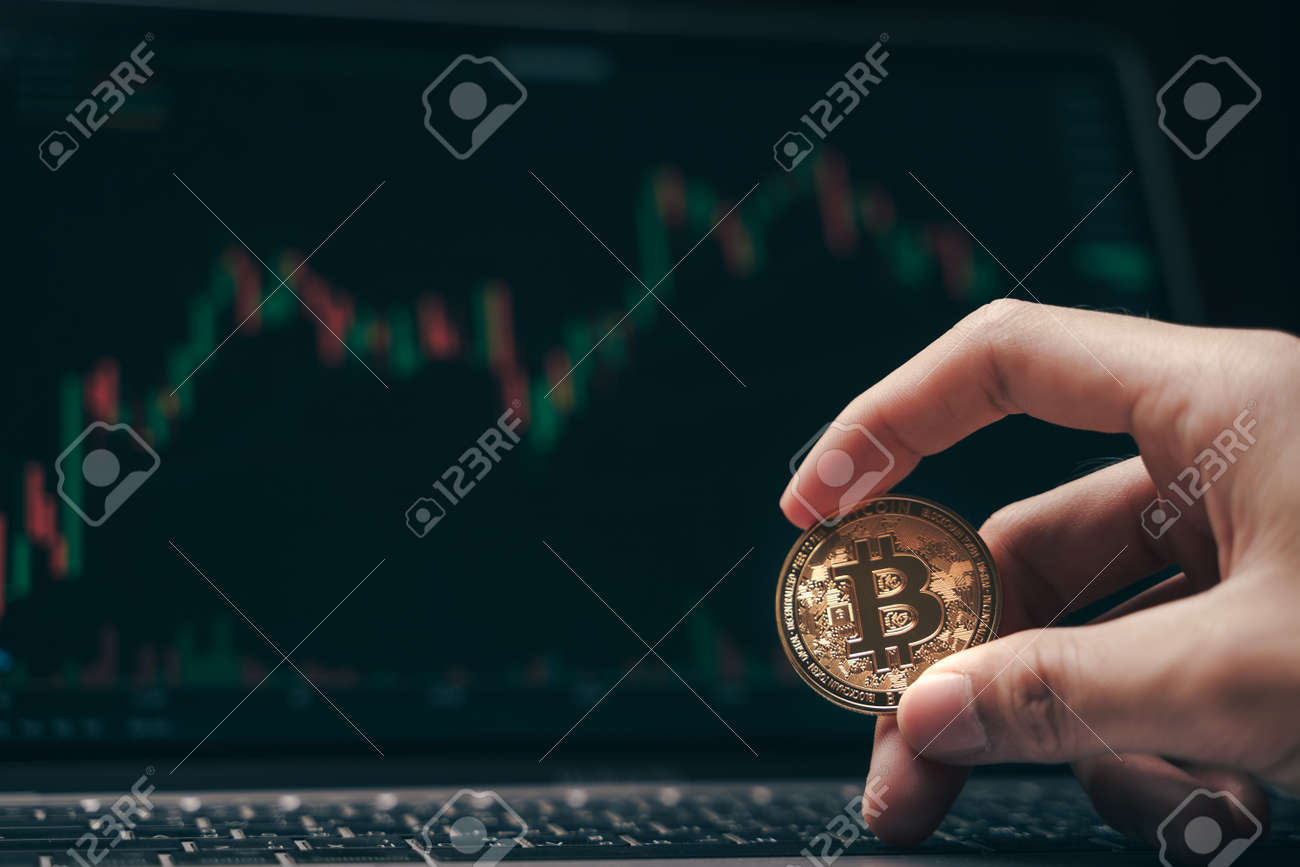 Businessman holding golden bitcoin on computer trading chart screen background. stock, cryptocurrency trading Concept. - 172185700