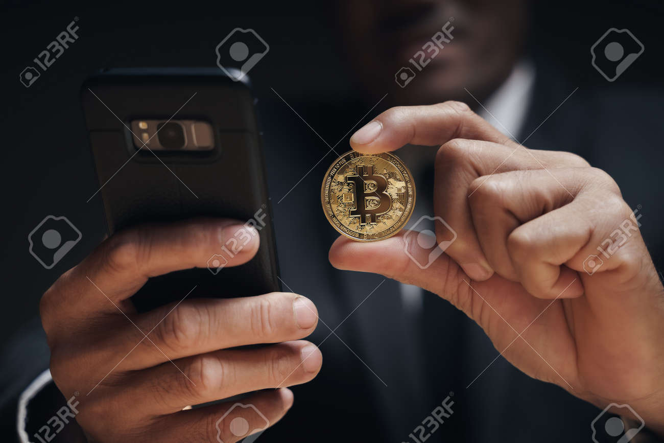 Businessman in black suit holding a golden bitcoin using Smartphone with Bitcoin trading chart on the screen to Trading Cryptocurrency, alternative finance and investment Concept. - 172185701