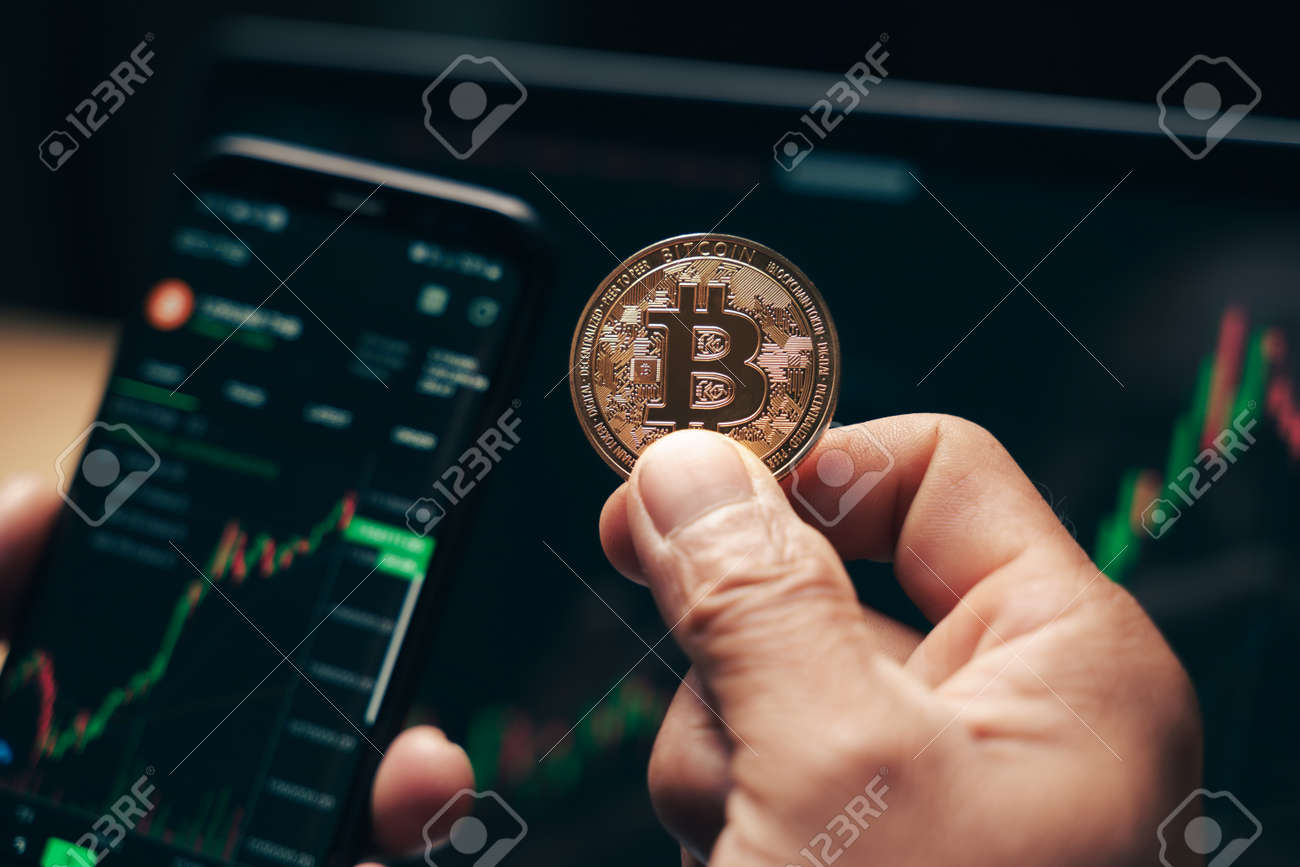 Businessman holding golden bitcoin on computer trading chart screen background. stock, cryptocurrency trading Concept. - 172185703