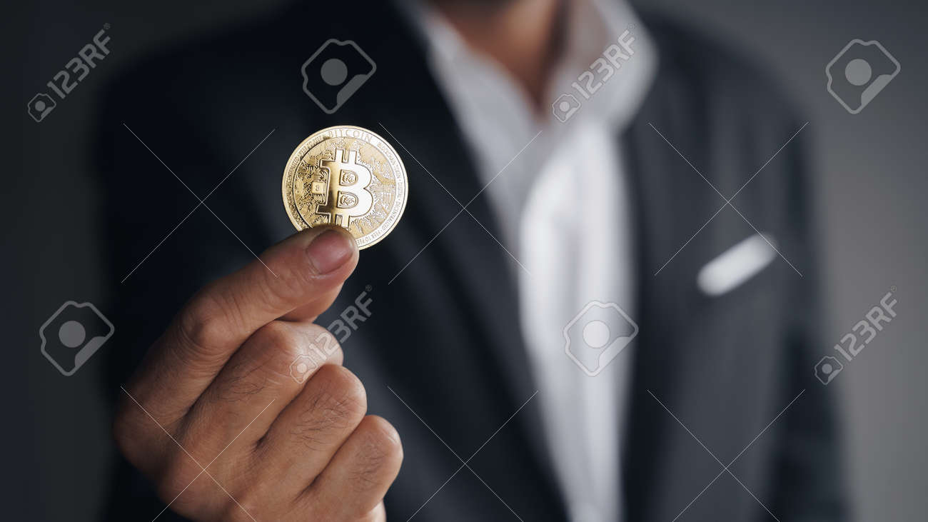 Handsome Investor Businessman in black suit holding a golden bitcoin on dark background, trading, Cryptocurrency, Digital virtual currency, alternative finance and investment Concept. - 172185705