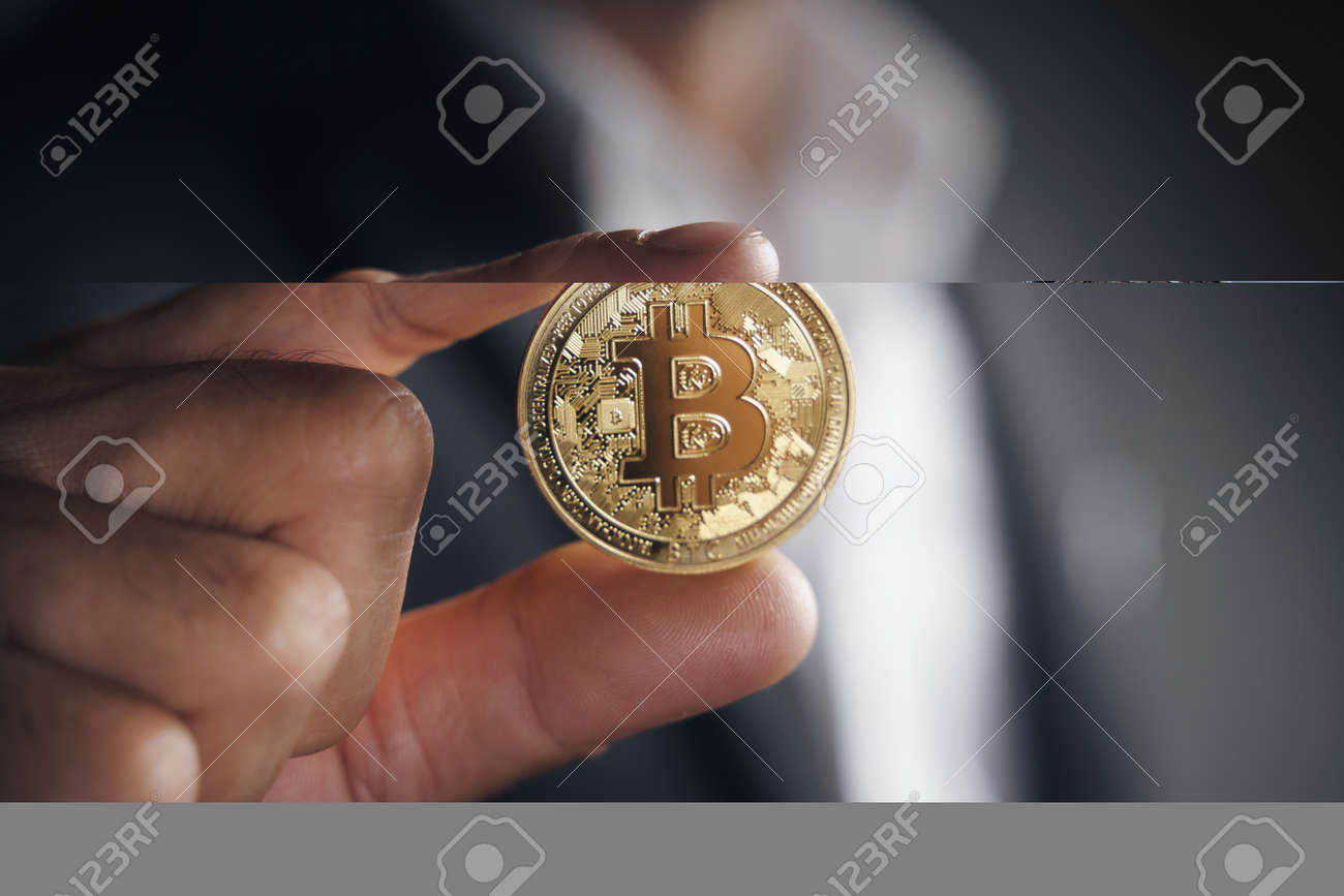 Handsome Investor Businessman in black suit holding a golden bitcoin on dark background, trading, Cryptocurrency, Digital virtual currency, alternative finance and investment Concept. - 172185712