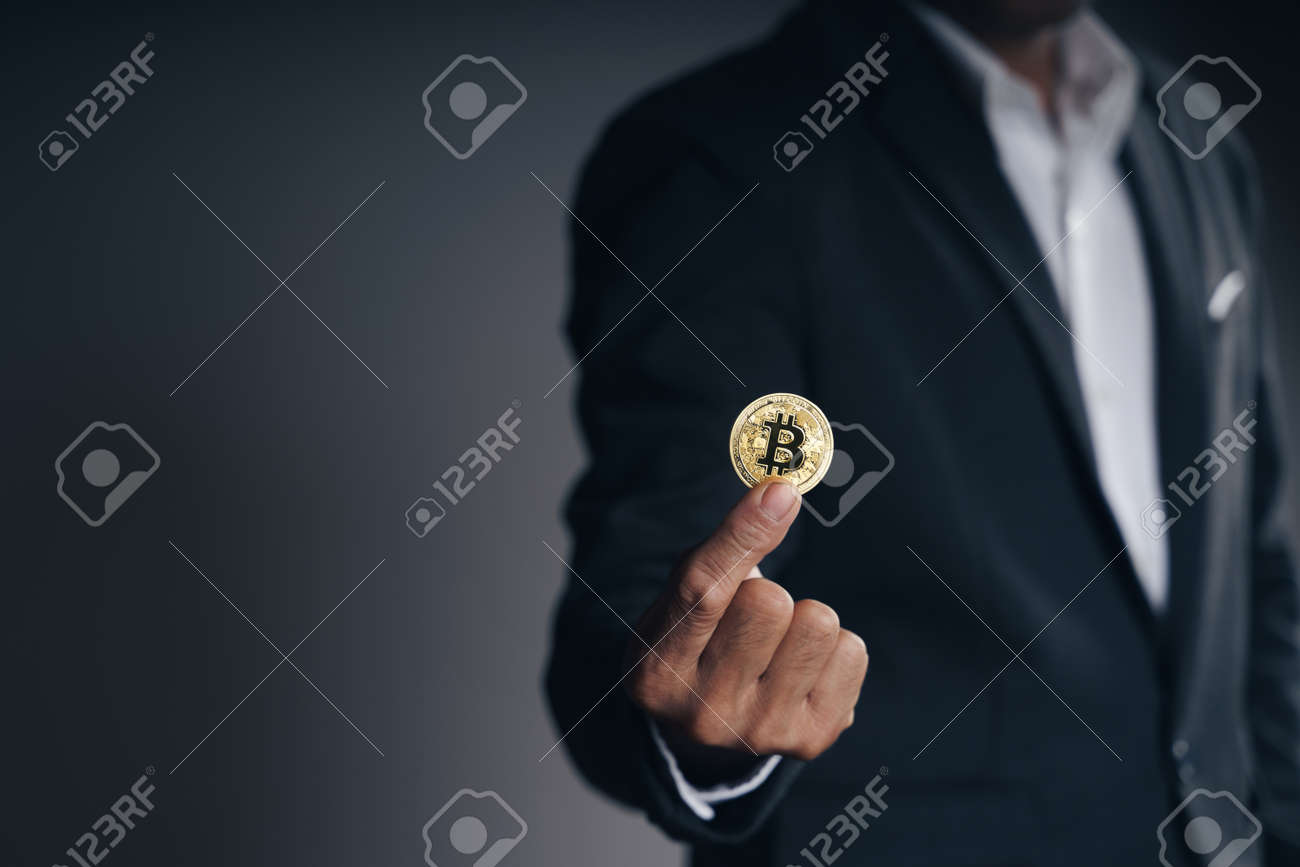 Handsome Investor Businessman in black suit holding a golden bitcoin on dark background, trading, Cryptocurrency, Digital virtual currency, alternative finance and investment Concept. - 172185713
