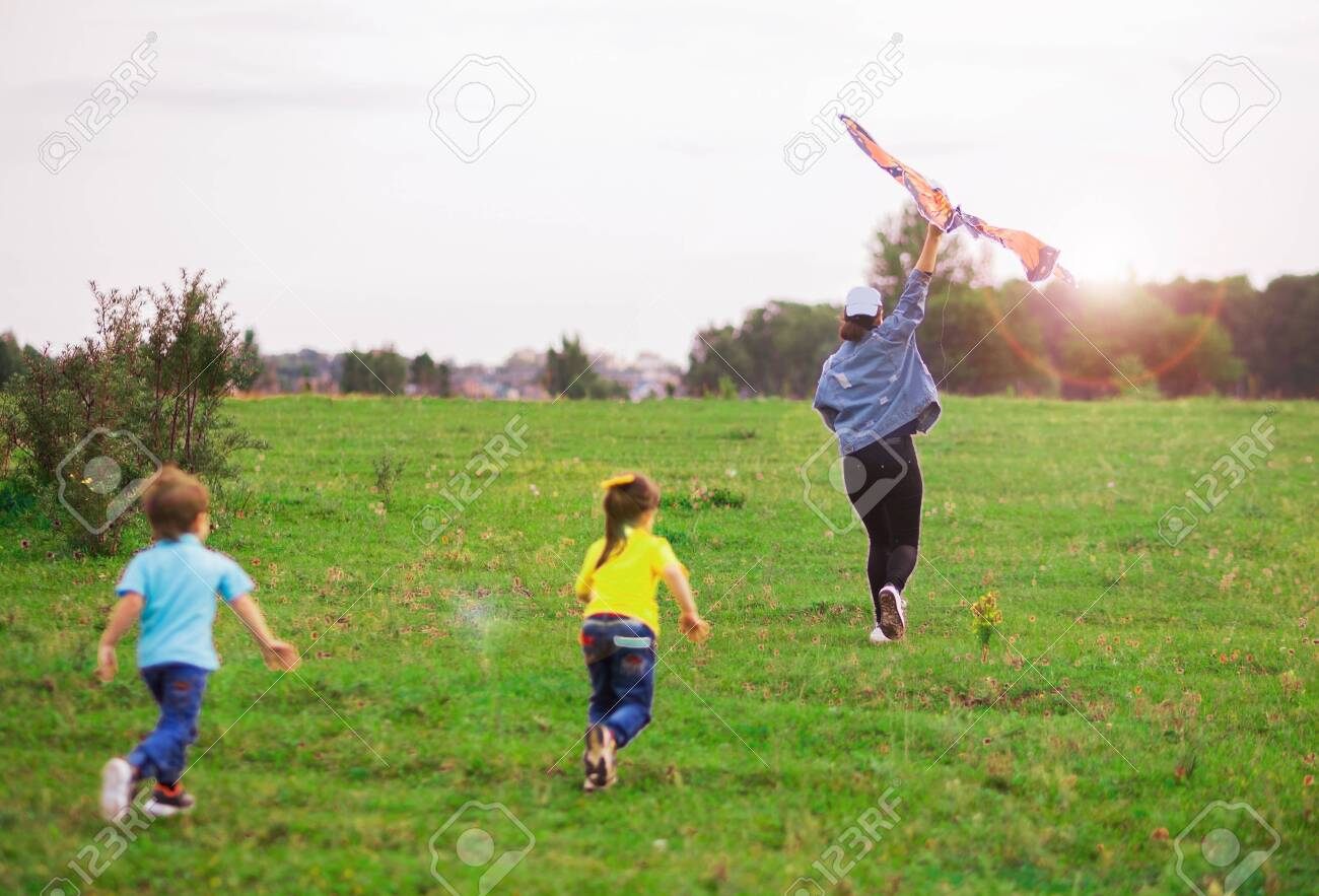 two children a boy in a blue T-shirt and a girl in yellow run for a kite into the distance. - 143580823