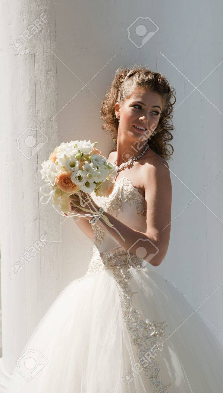 The bride with a bouquet. The bride in a wedding dress with a bouquet on the white. - 10422148