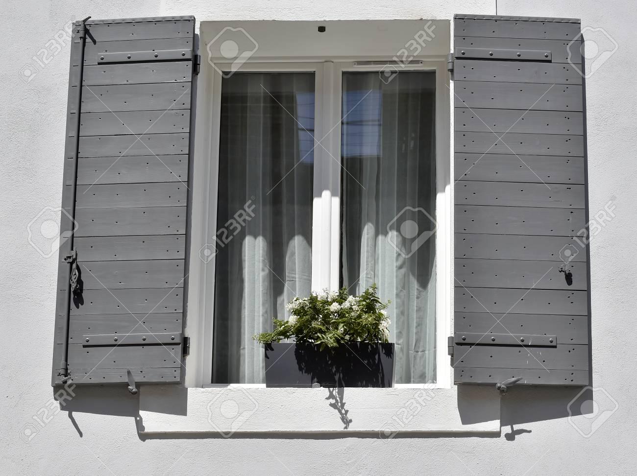 Maison Grise Avec Des Fenêtres Blanches Et Des Fleurs Blanches En Pot
