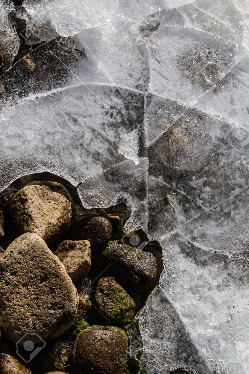 Frozen pond with cracks, bubbles, rocks and ice creating a network of textures and lines Stock Photo - 16540938