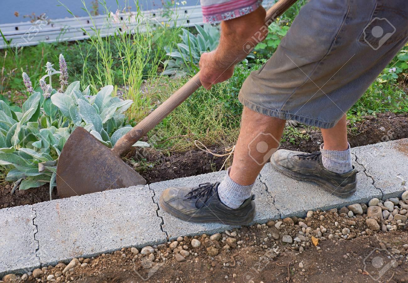 senior gärtner, der eine wand fundament im garten bauen lizenzfreie