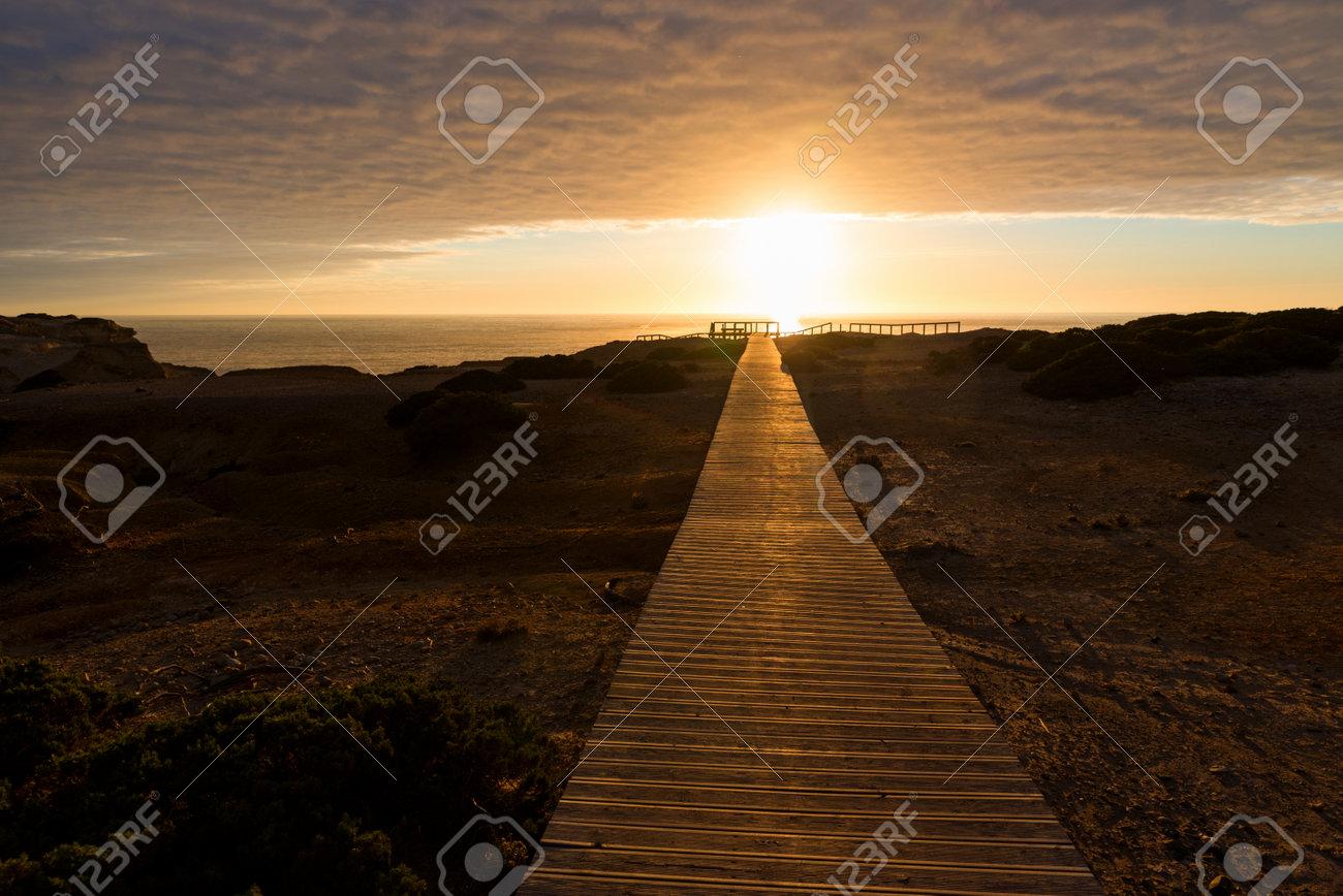 wooden boardwalk at sunset, coastal landscape Carrapateira West Algarve. cloudy sky and sunshine - 161314826