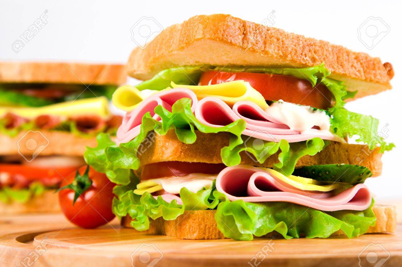 big sandwich with fresh vegetables on wooden board on white background Stock Photo - 11814349