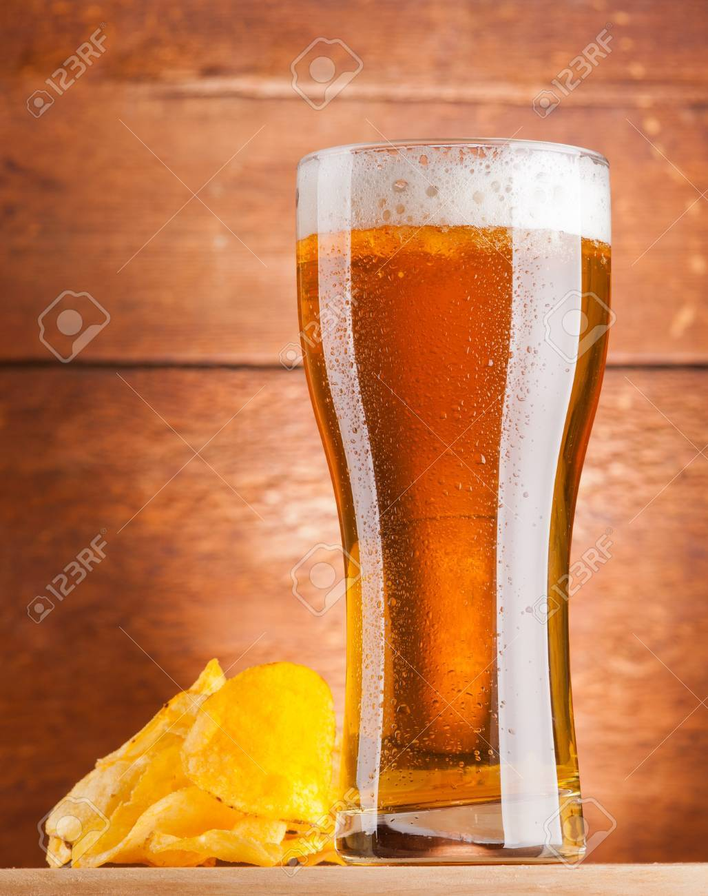 glass of fresh golden beer with potato chips Stock Photo - 12185513