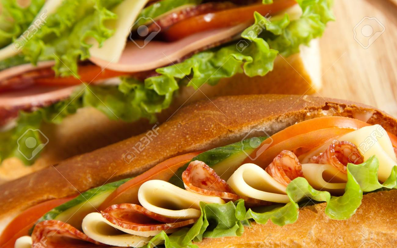 big sandwich with fresh vegetables on wooden board Stock Photo - 12921878