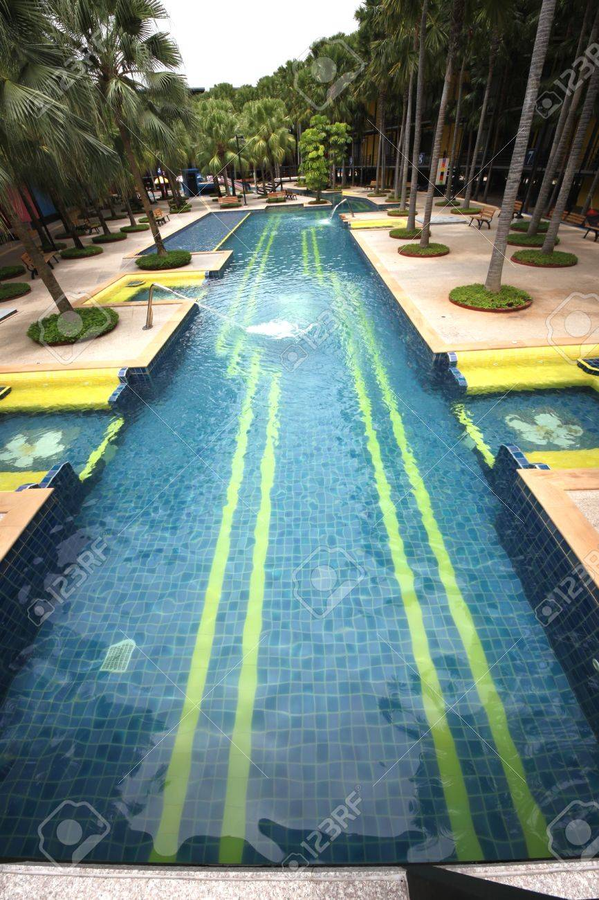 A Big Swimming Pool With Clear Water And Seats In Water In The