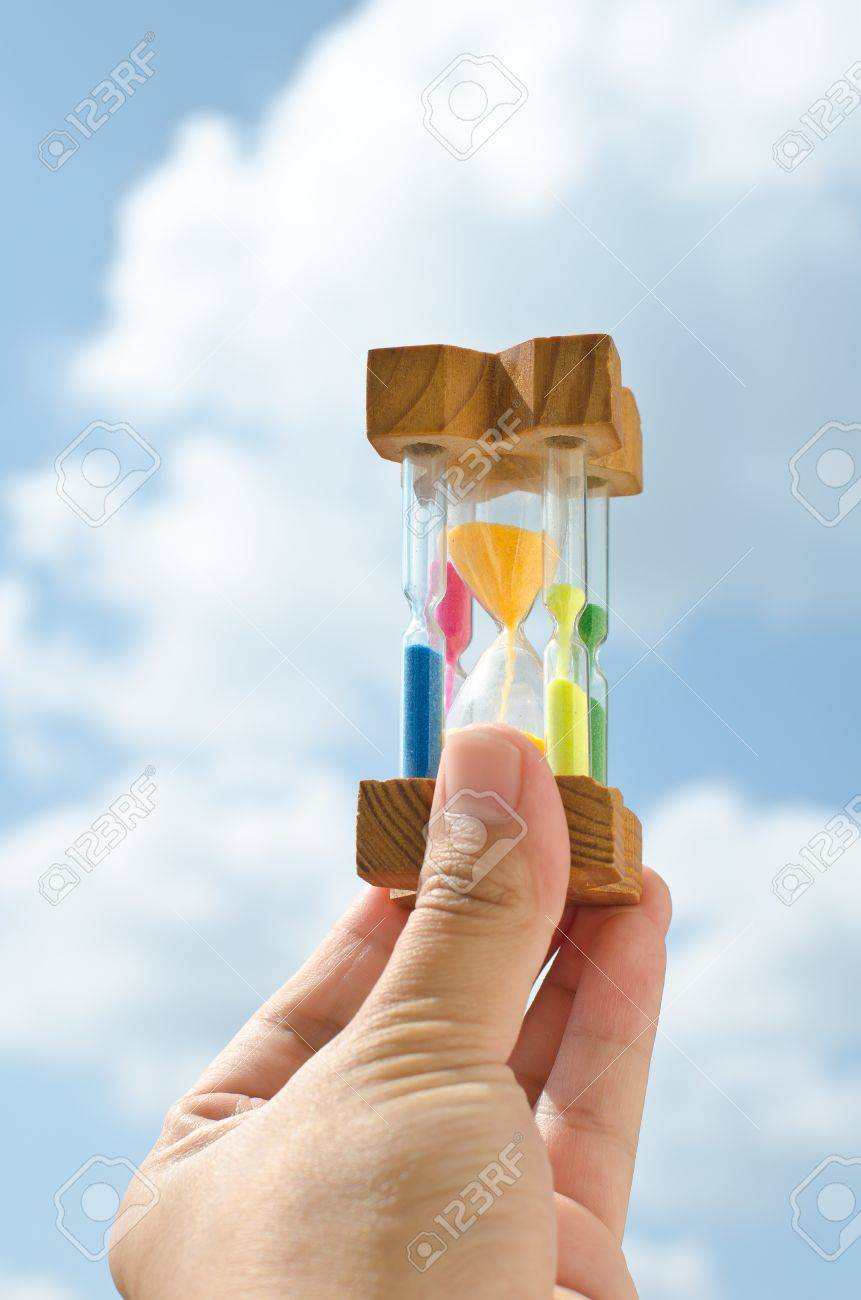 Colorful hourglass sand timer in hand of man on the sky Stock Photo - 12058076