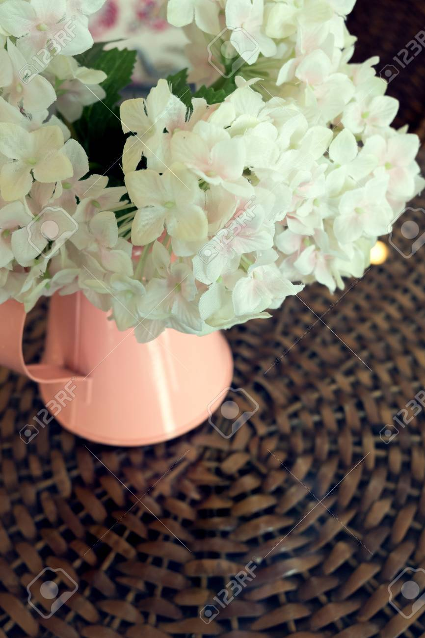 White Plastic Flowers In Pink Flower Vase On The Rattan Weave