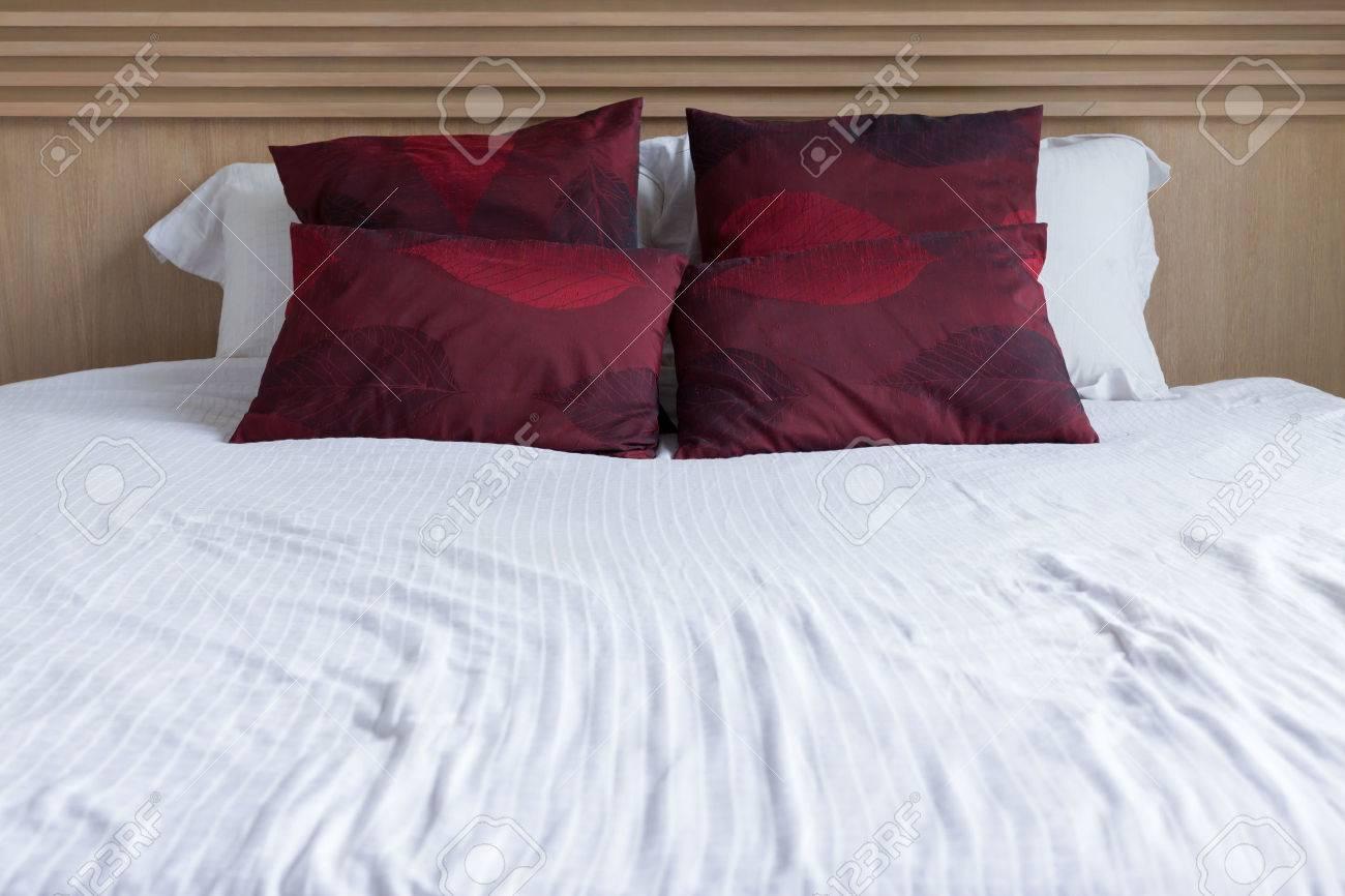 Sovrum inredning modern stil med vit madrass och röd kudde och trä ...