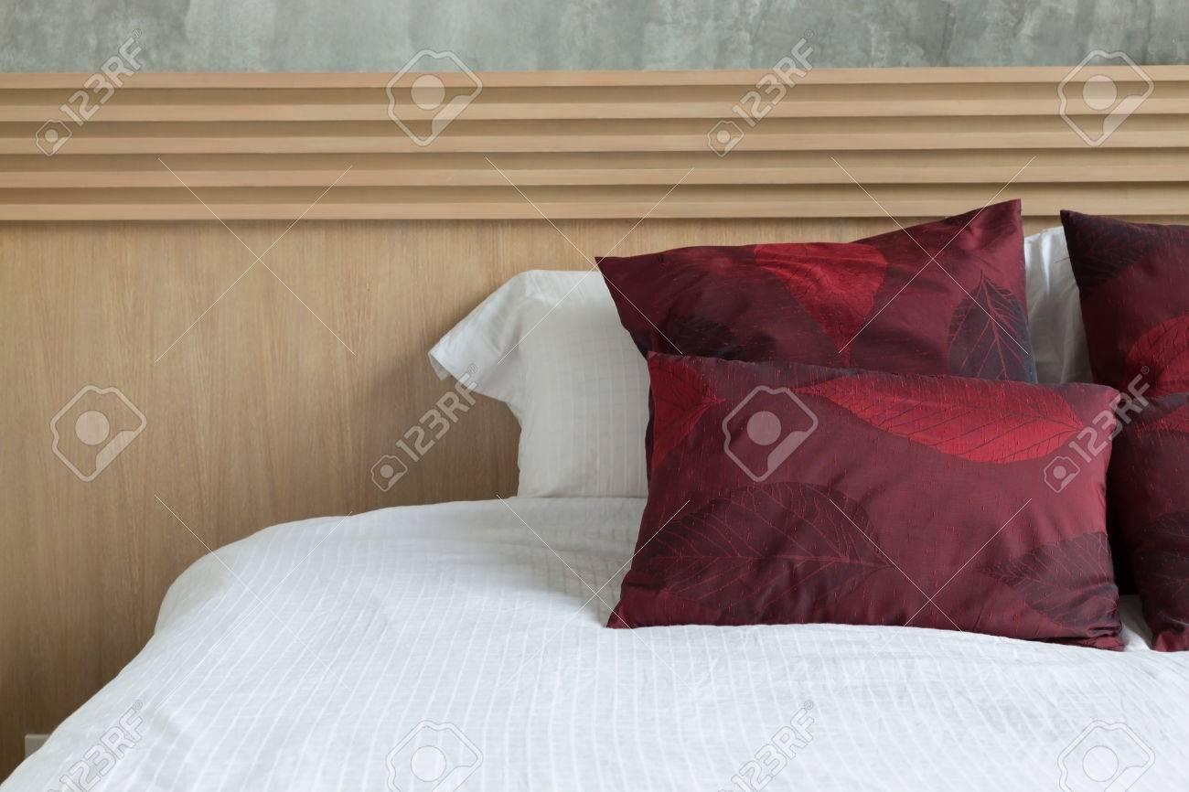 Camera da letto design di stile interni moderni con materasso bianco e  cuscino rosso e testata in legno