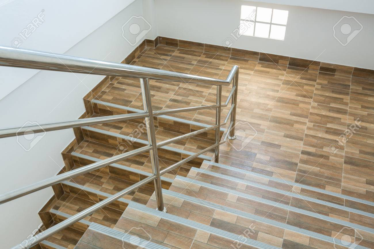 Staircase in residential house with stainless steel banister staircase in residential house with stainless steel banister ceramic floor tiles wood pattern stock photo dailygadgetfo Image collections