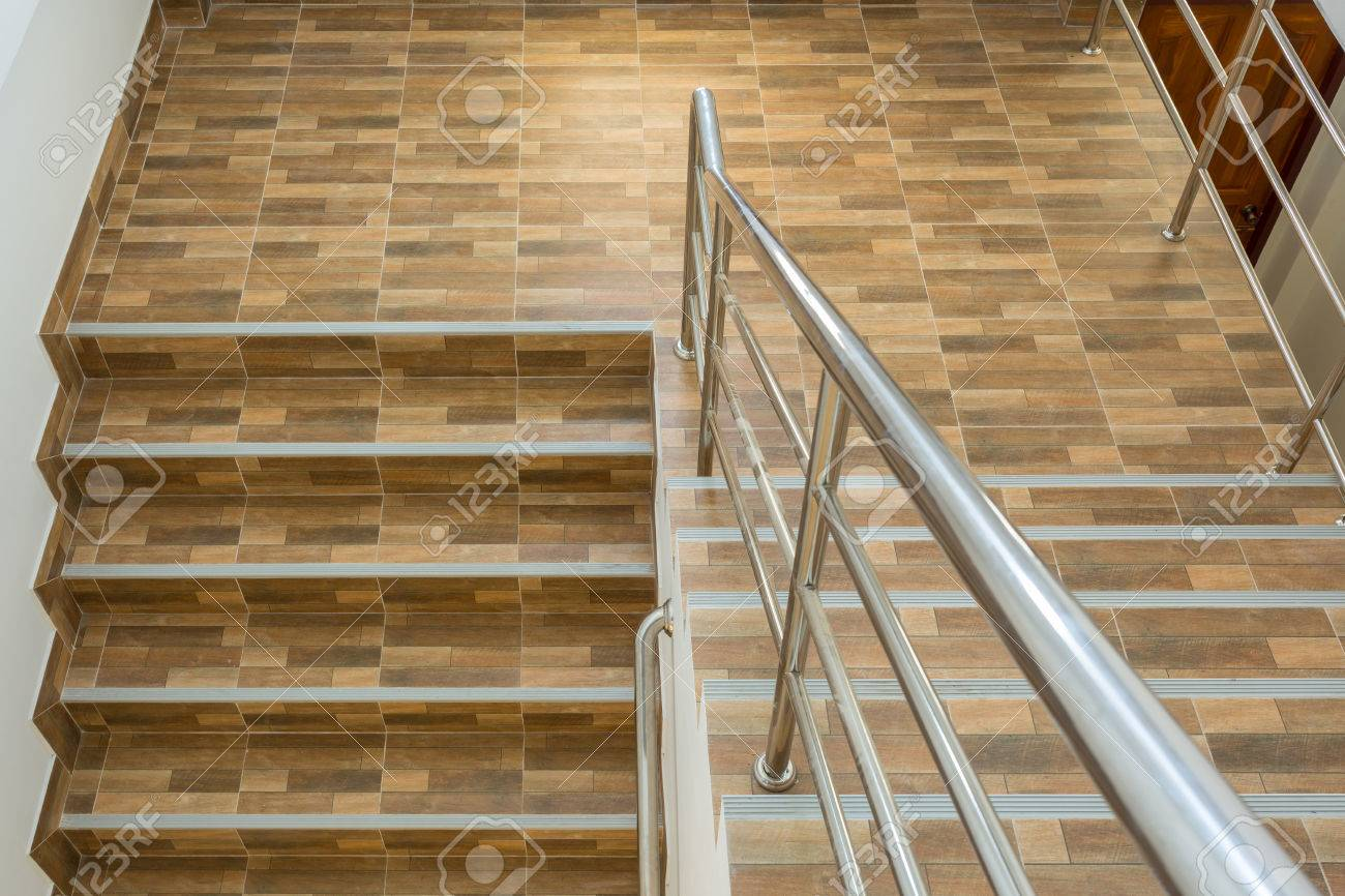 Staircase in residential house with stainless steel banister staircase in residential house with stainless steel banister ceramic floor tiles wood pattern stock photo dailygadgetfo Choice Image