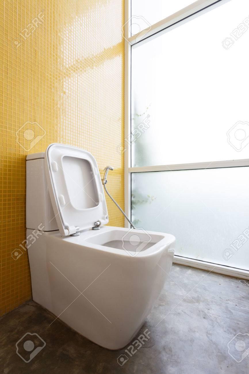 Blanc chasse d\'eau et jaune décoration murale en mosaïque dans salle de  bains moderne entre la maison