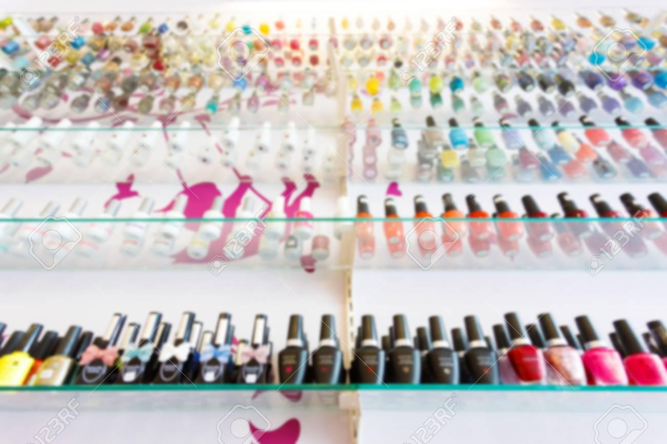 fashion colorful manicure nail polish bottle collection set on glass display shelf, blur interior beauty