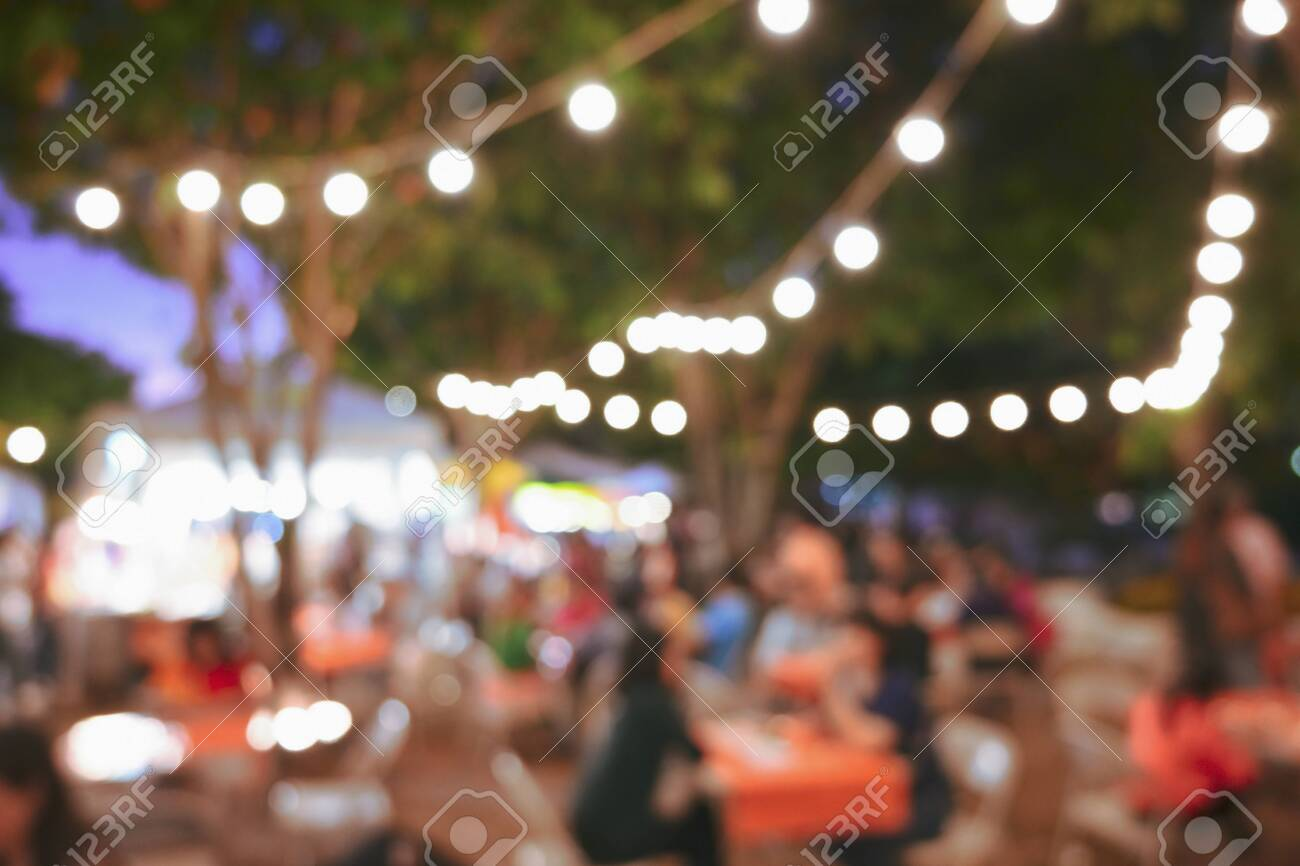 people crowd in night party festival of outdoor garden with light bulb hanging decoration, image blur used for celebration background - 137892416