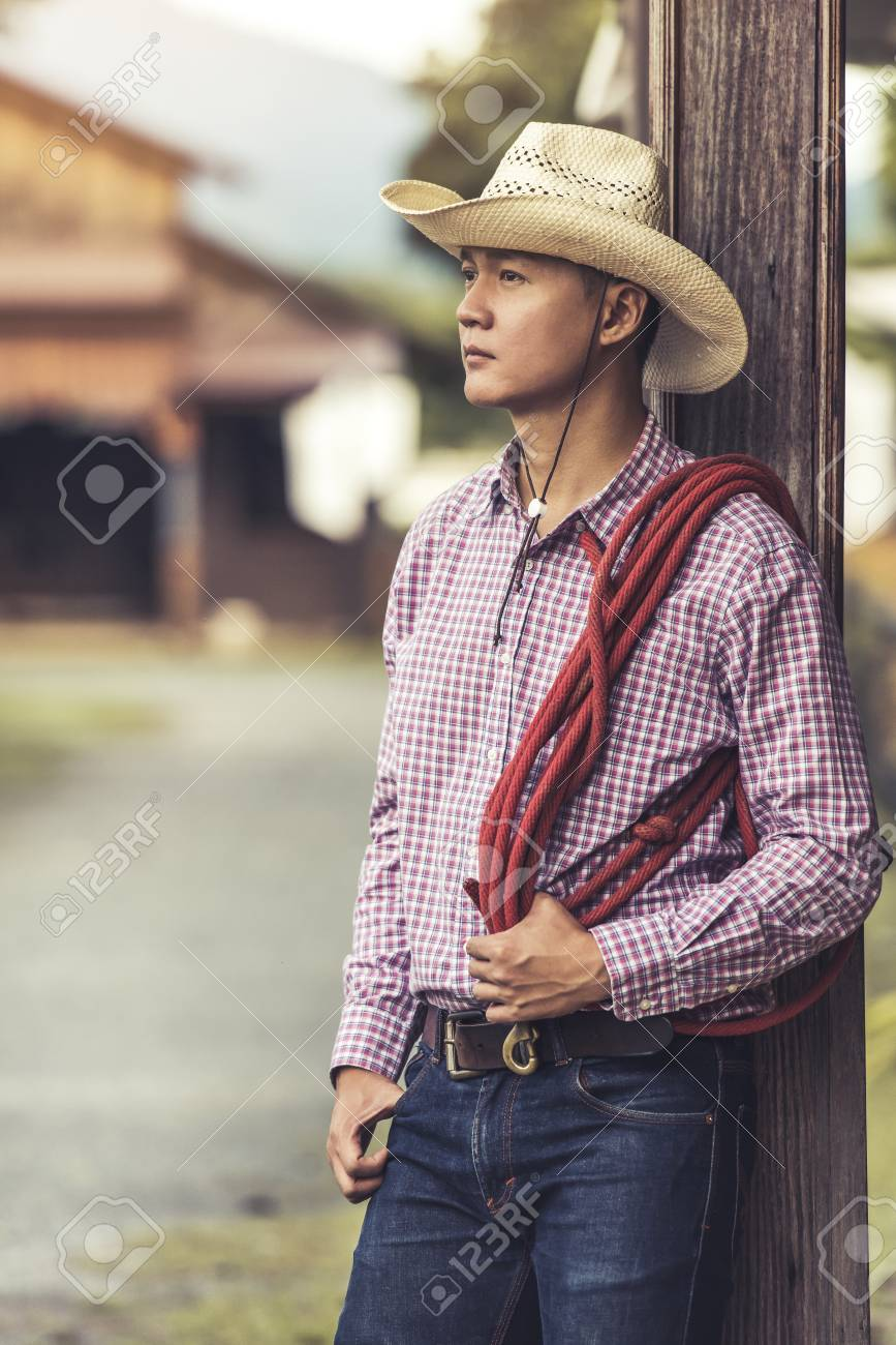Handsome young man wearing cowboy hat scott shirt and blue jean trousers  standing thinking Stock Photo 856fc21c669