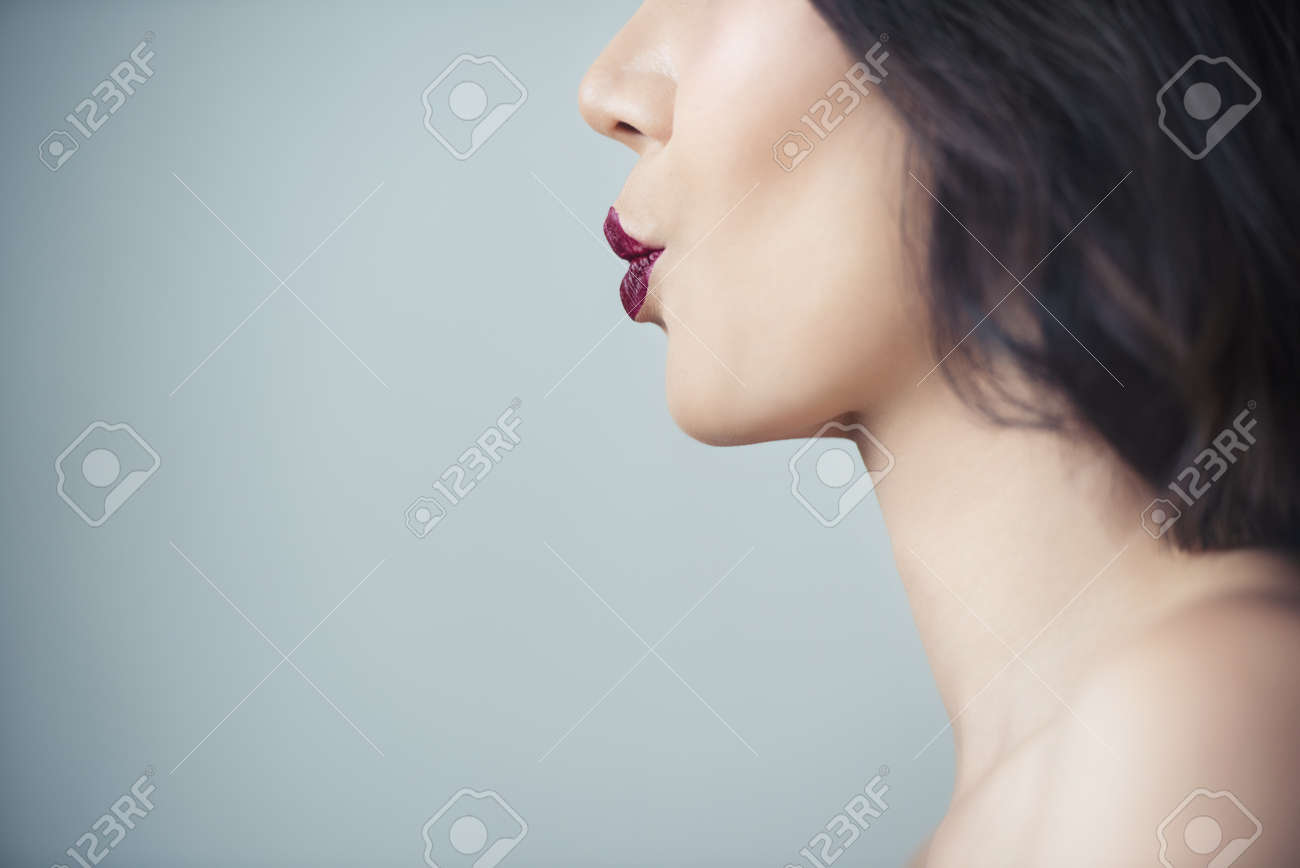Makeup artist applies red lipstick . Beautiful woman face. Hand of make-up master, painting lips of young beauty model girl . Make up in process - 165410436