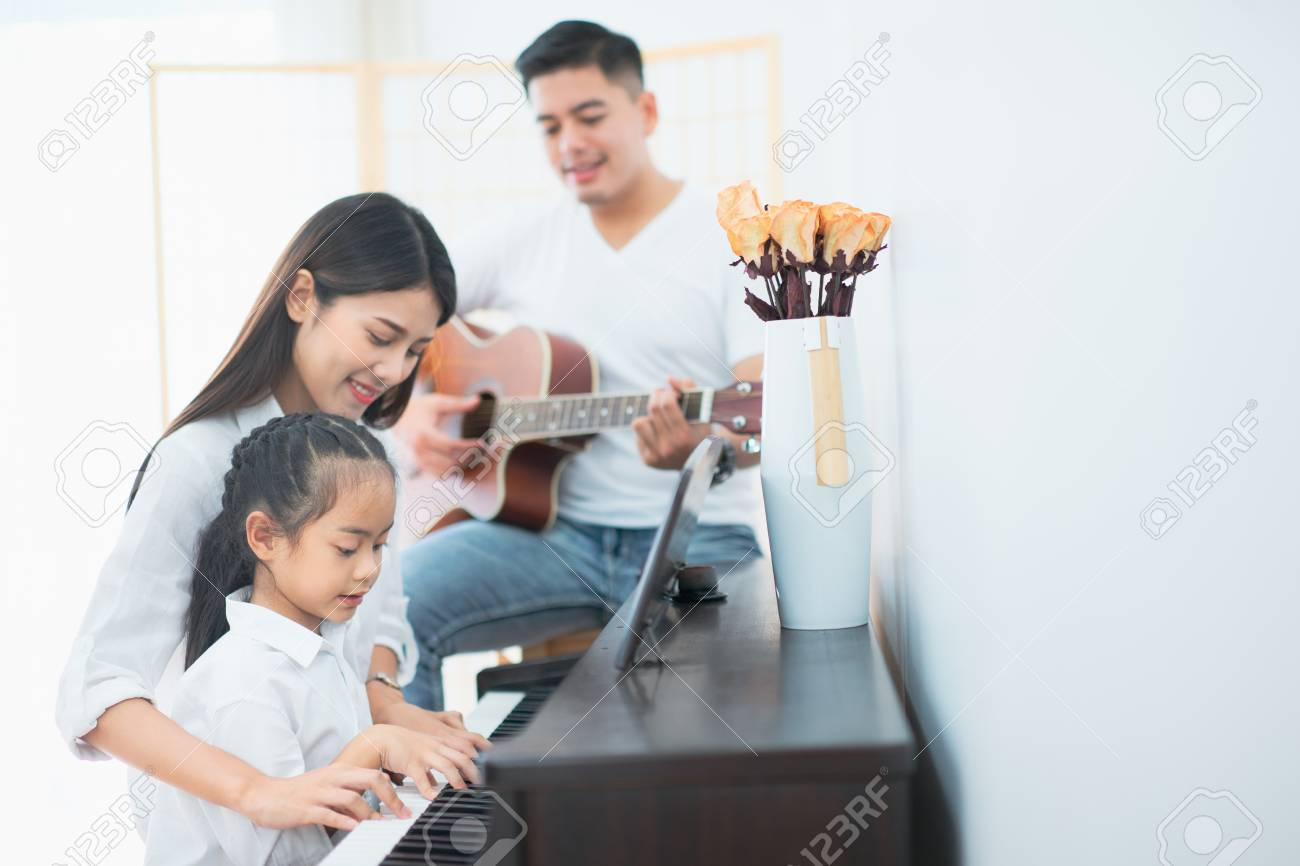Asian family, Mother and daughter playing piano,Father playing