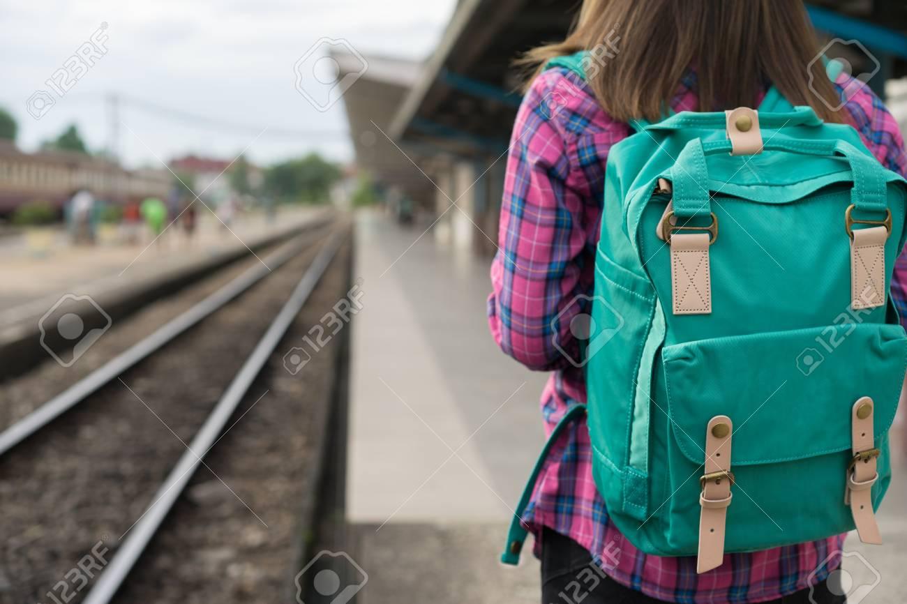 Traveler woman walking and waits train on railway platform, Sun light flare, Selective focus - 104435654