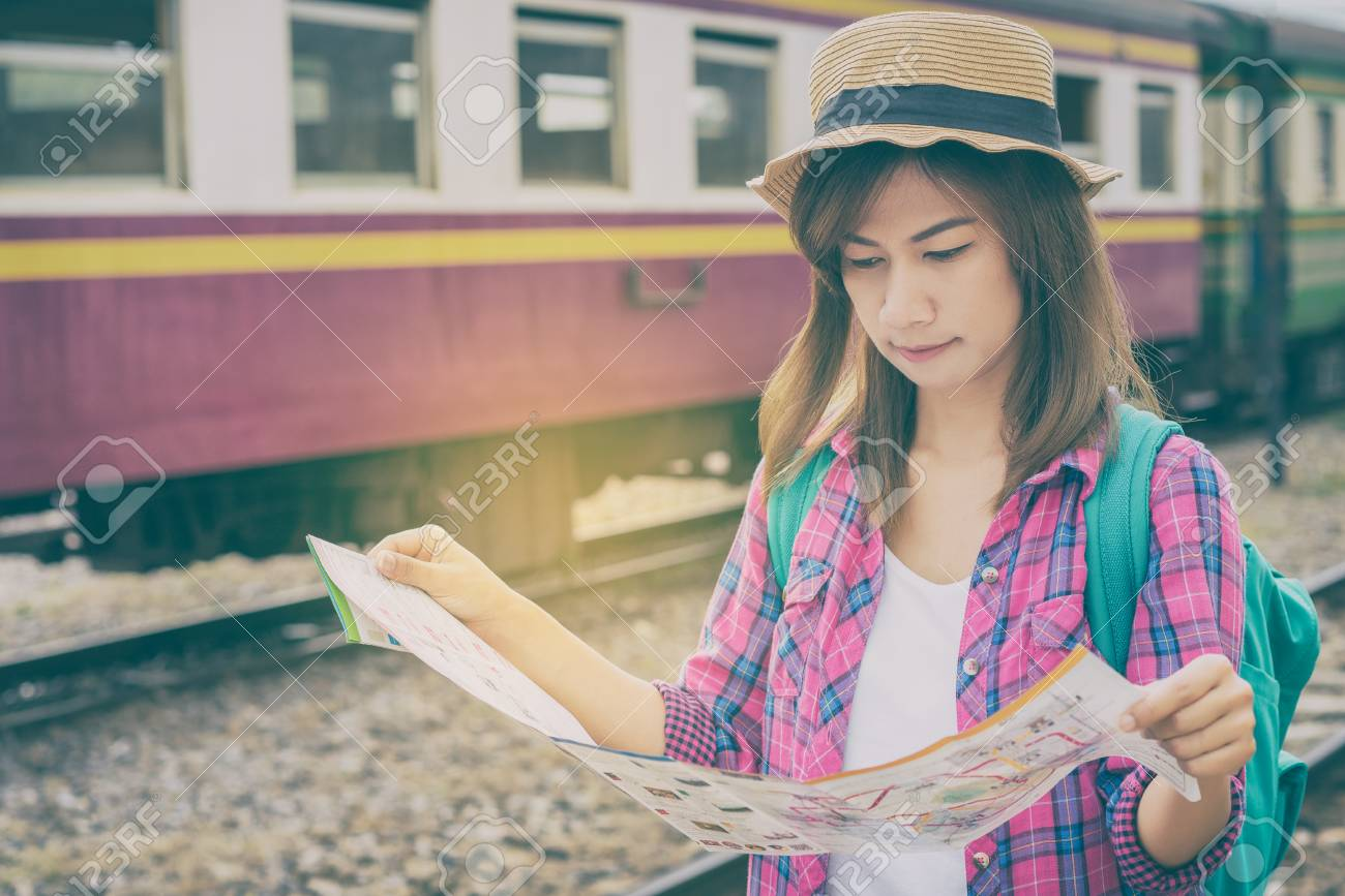 Young woman traveler with backpack and hat at the train station and looking on the map for plan to travel, Travel concept - 104430536