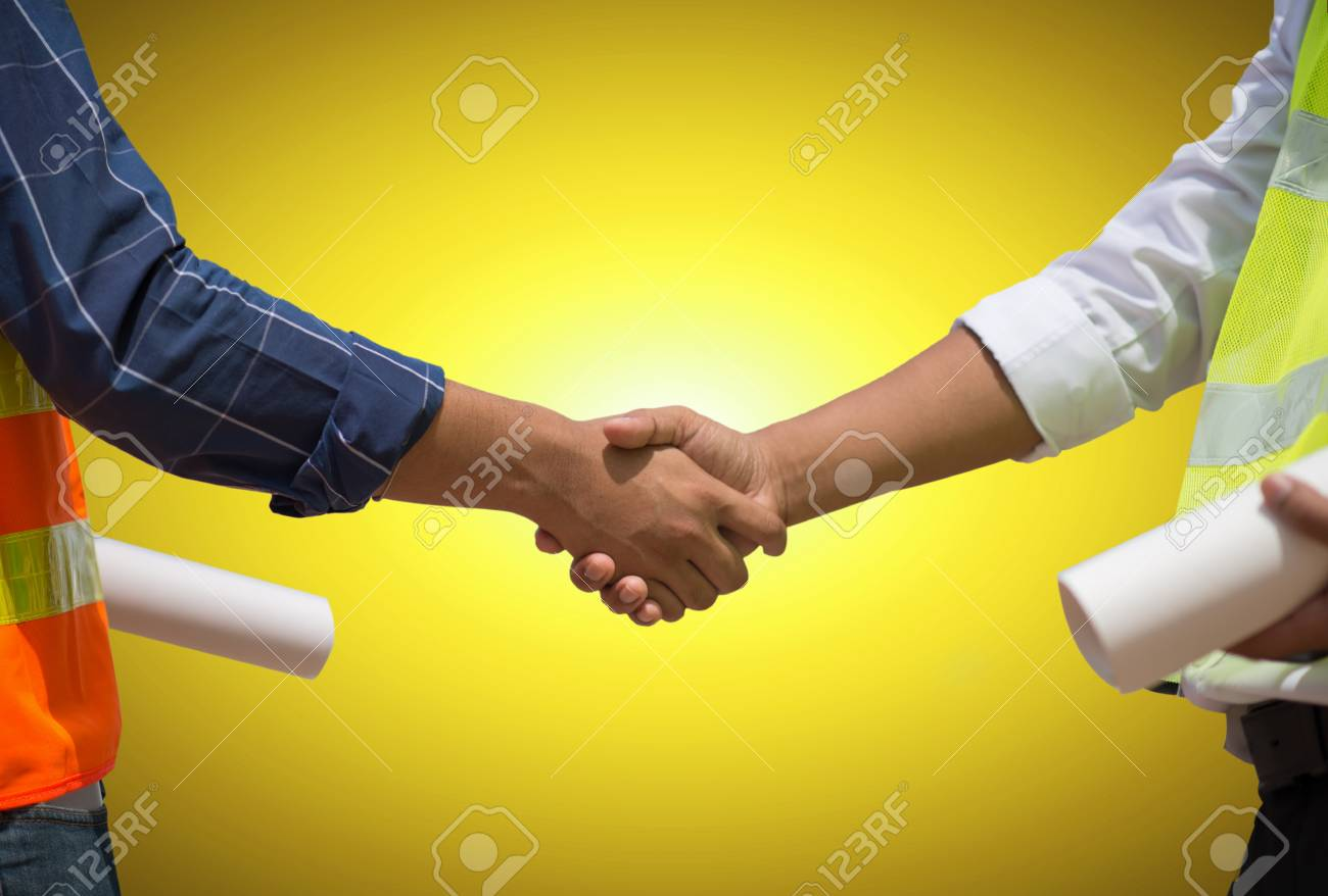Handsome construction workers in protective helmets and vests are shaking hands while working in the office center, Horizontal, Blurred background - 104430270