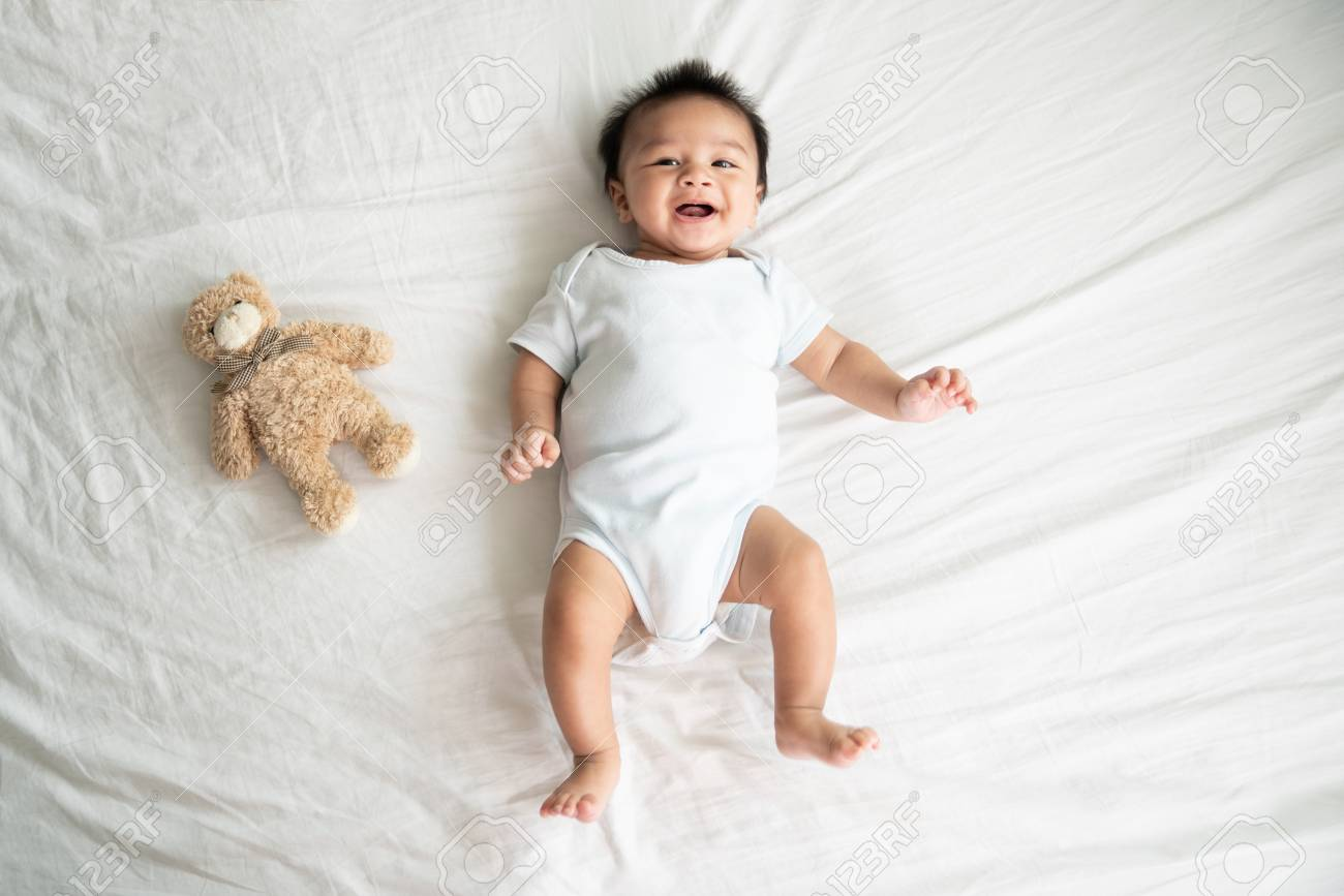 Portrait of a crawling baby on the bed in her room, Adorable baby boy in white sunny bedroom, Newborn child relaxing in bed, Nursery for young children, Textile and bedding for kids - 110614659