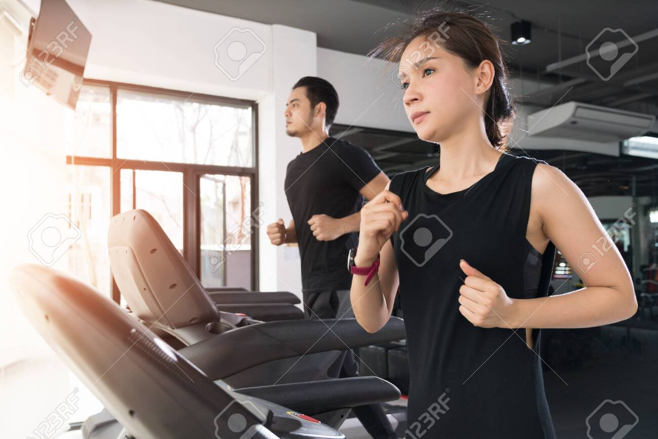 Running on treadmills, Active young woman and man running on treadmill in gym - 110615588