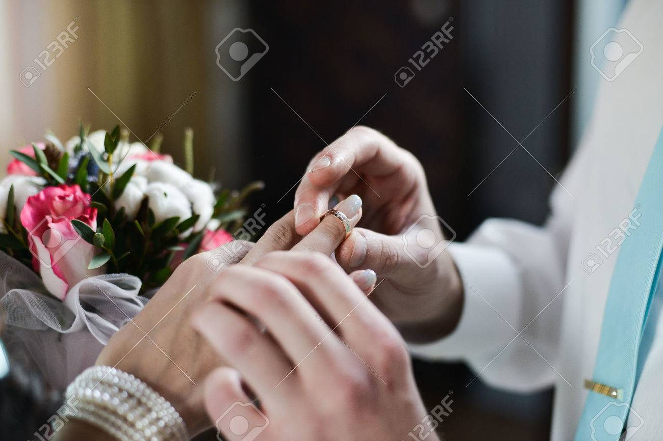 Man Wears Wedding Ring On The Hand Of The Woman Stock Photo Picture