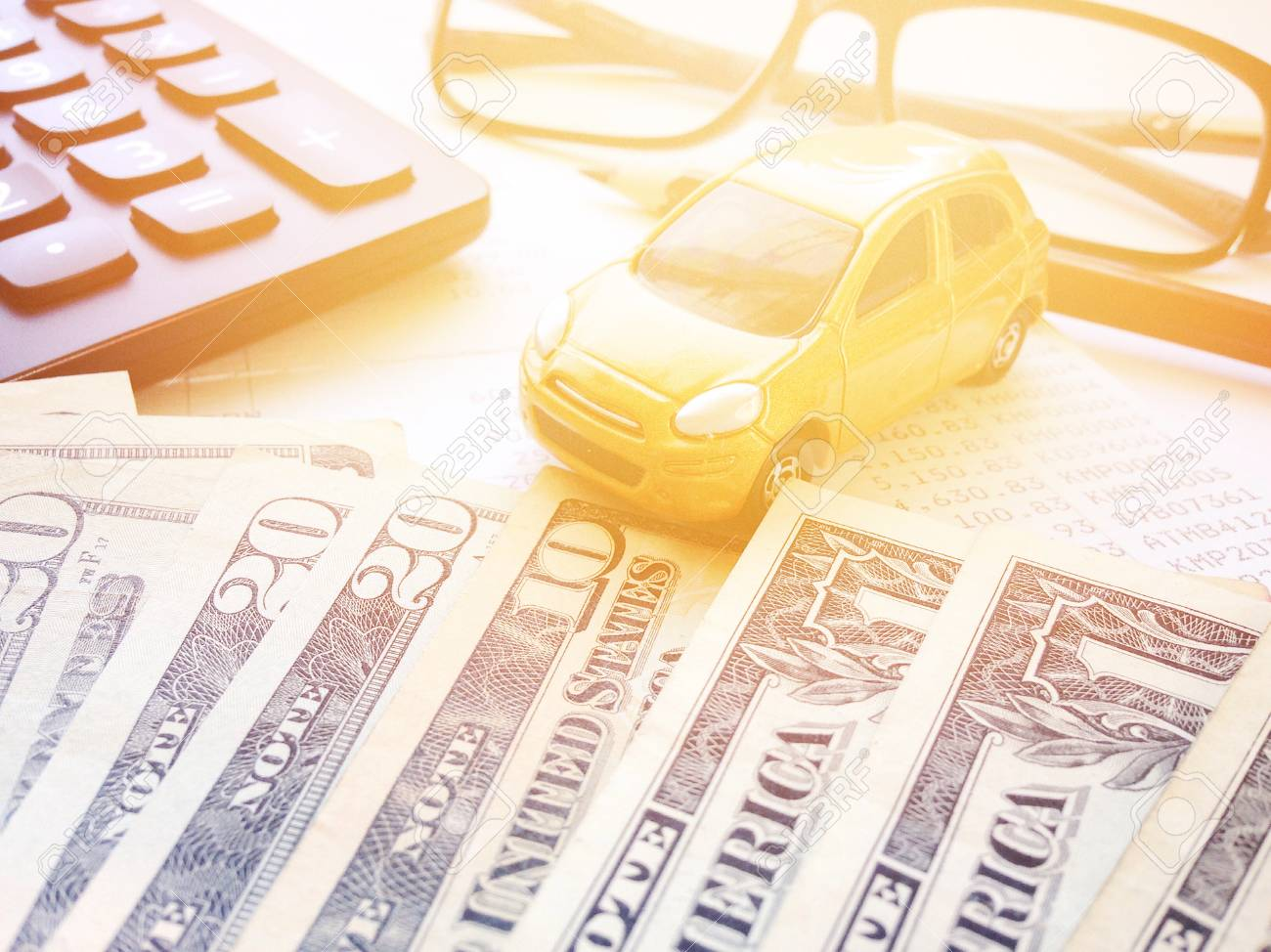 Business, finance, saving money or car loan concept : Miniature car model, American Dollars cash money, calculator and saving account book or financial statement on office desk table - 126599871