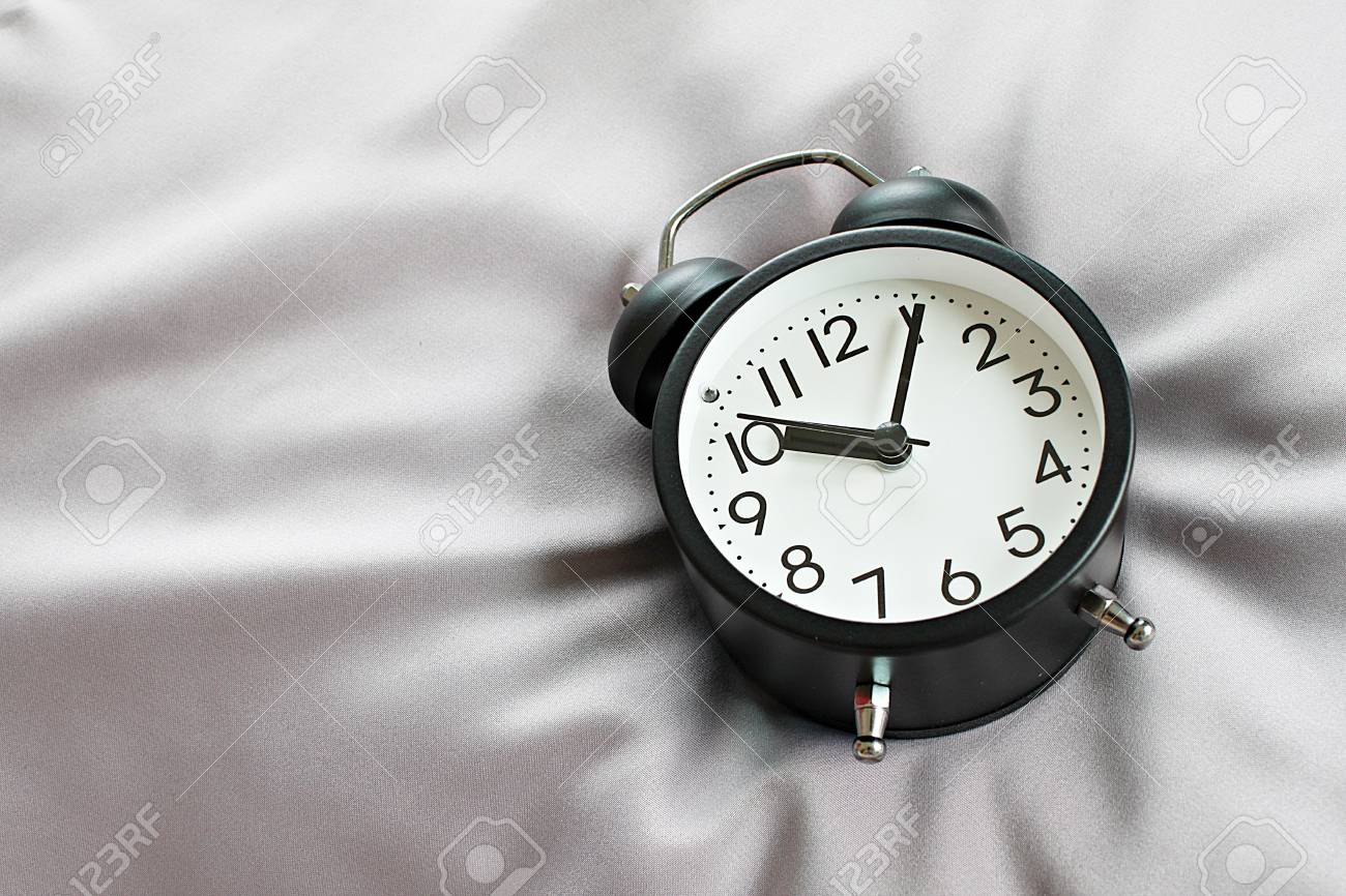 Still life, business deadline, meeting, time management, savings time, relax, weekend or holiday concept concept : Top view of black retro alarm clock on bed in morning, ready for adding or mock up - 126599879
