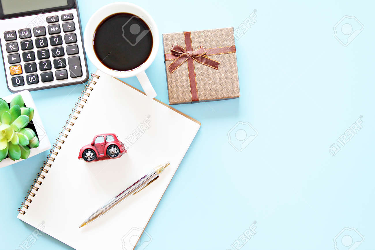Top view or flat lay of notebook paper with pen, calculator, clock and coffee cup - 168796792