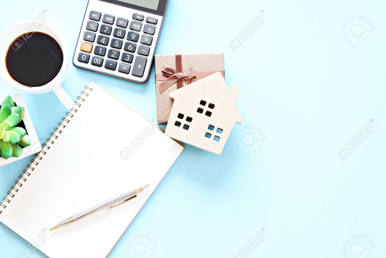 Top view or flat lay of notebook paper with pen, calculator, clock and coffee cup - 168796801