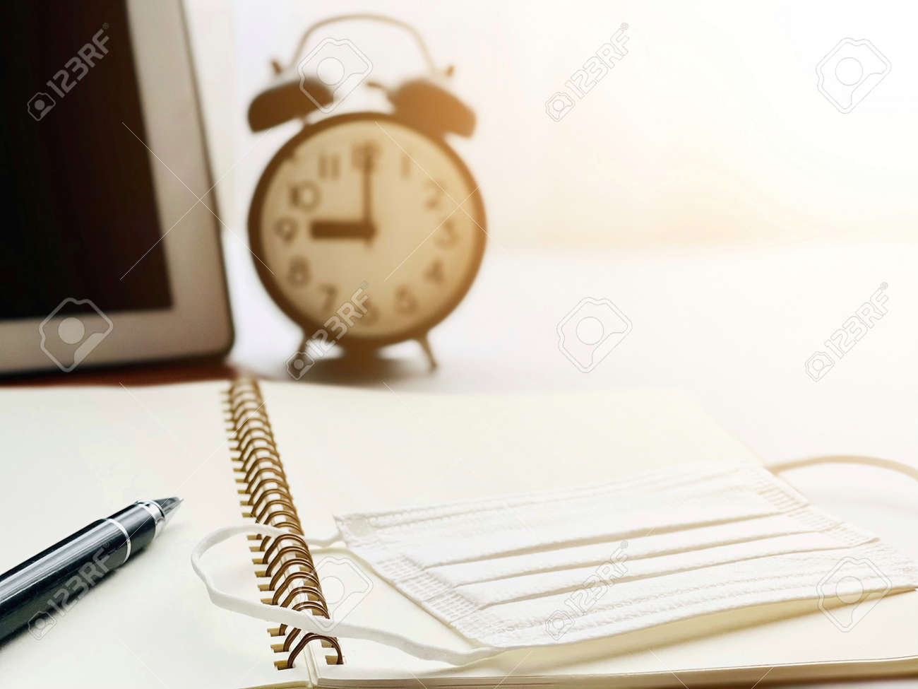 Anti virus protection mask on open notebook paper, digital tablet and clock on working desk table - 168796800