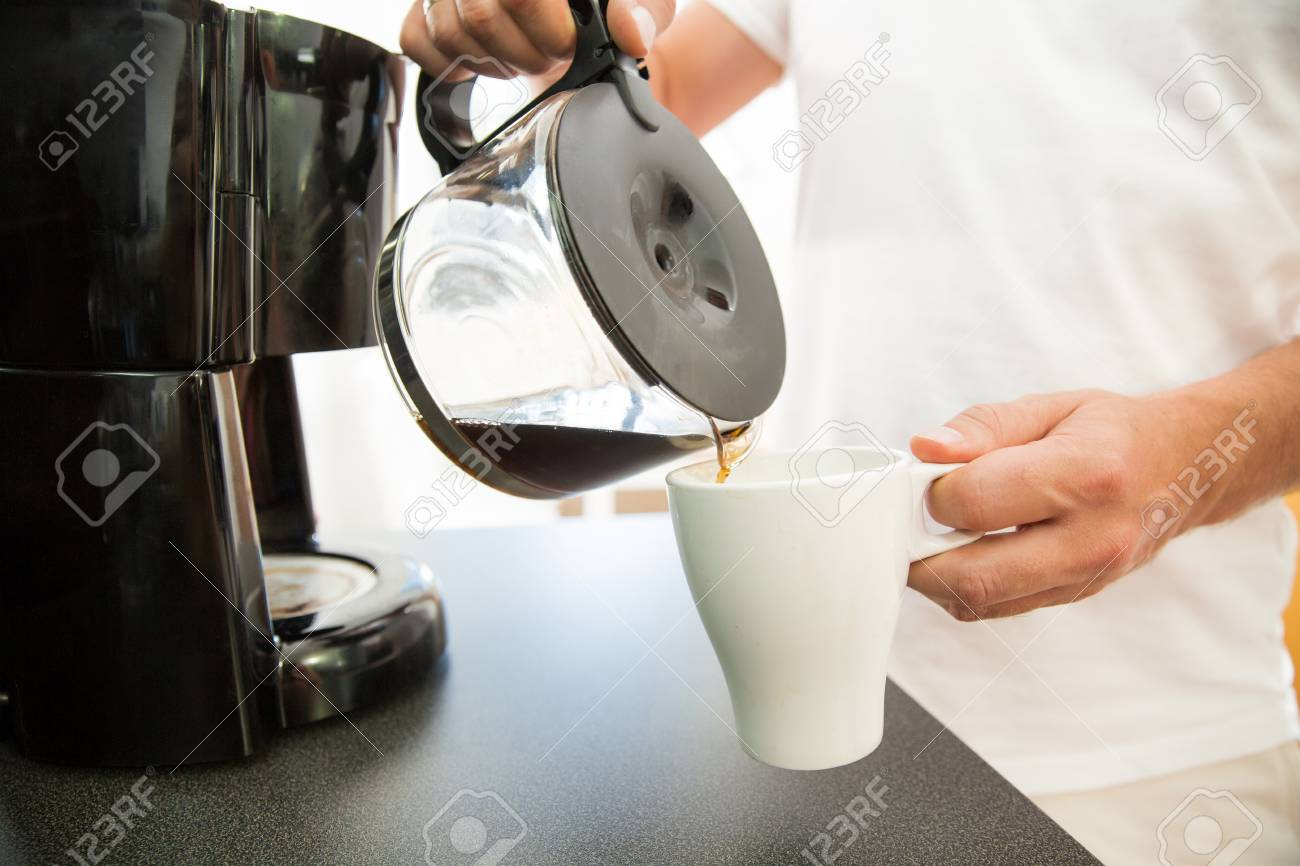 Man In The Kitchen Pouring A Mug Of Hot Filtered Coffee From.. Stock ...