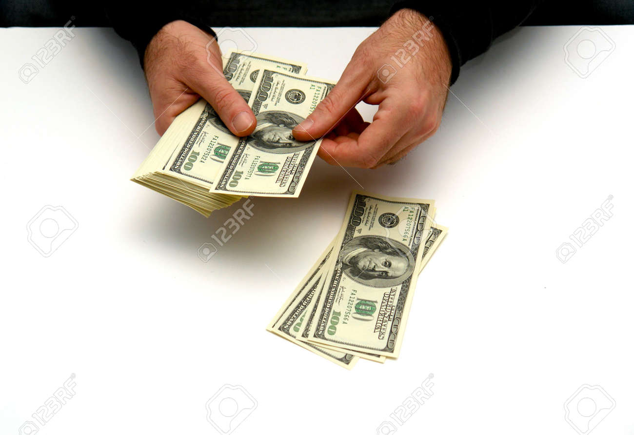 worksheet Counting Dollar Bills man counting out hunderd dollar bills in three stacks on white table stock photo 2329210