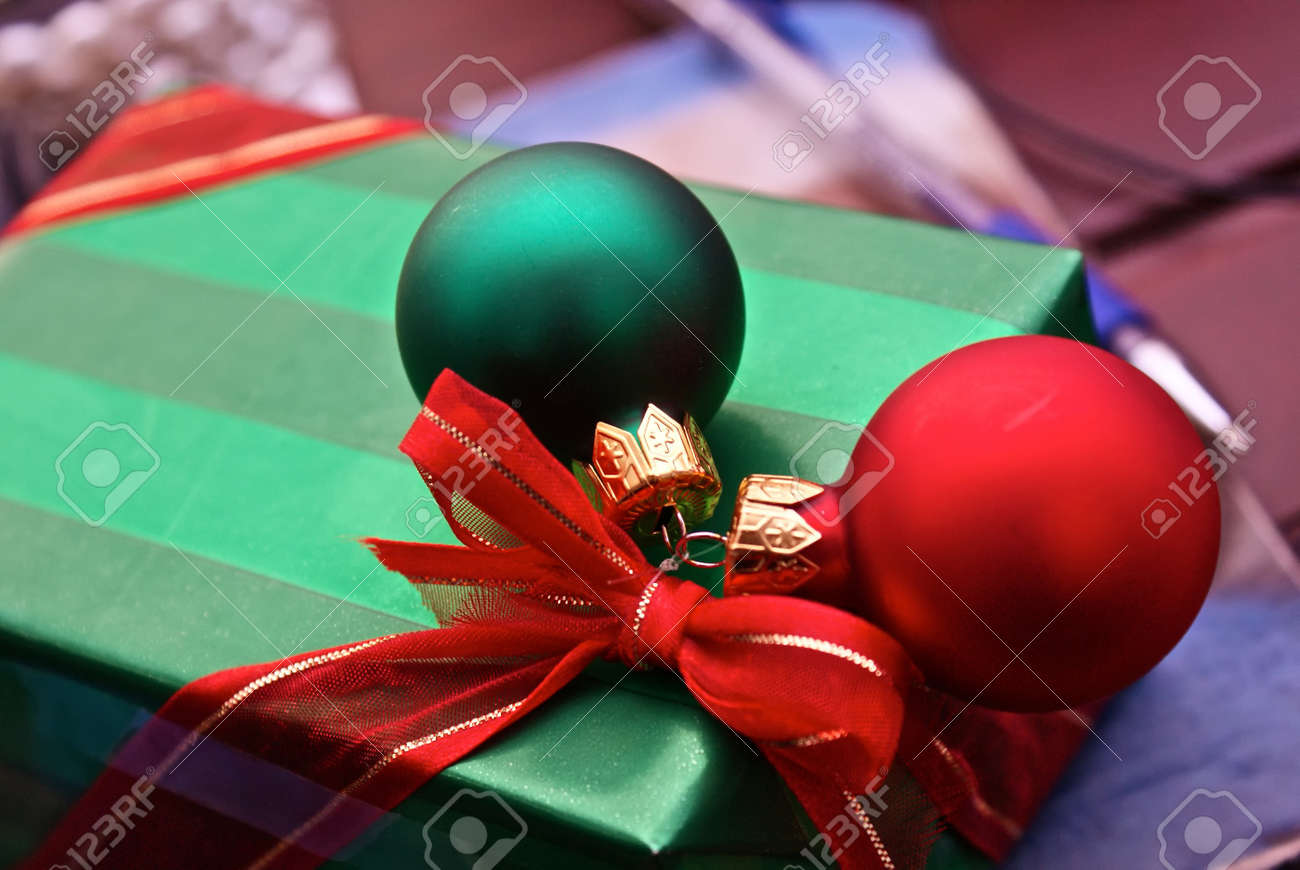 beautifully wrapped and well adorned christmas present with ornaments and red bow with pen and notebook in background Stock Photo - 4065530
