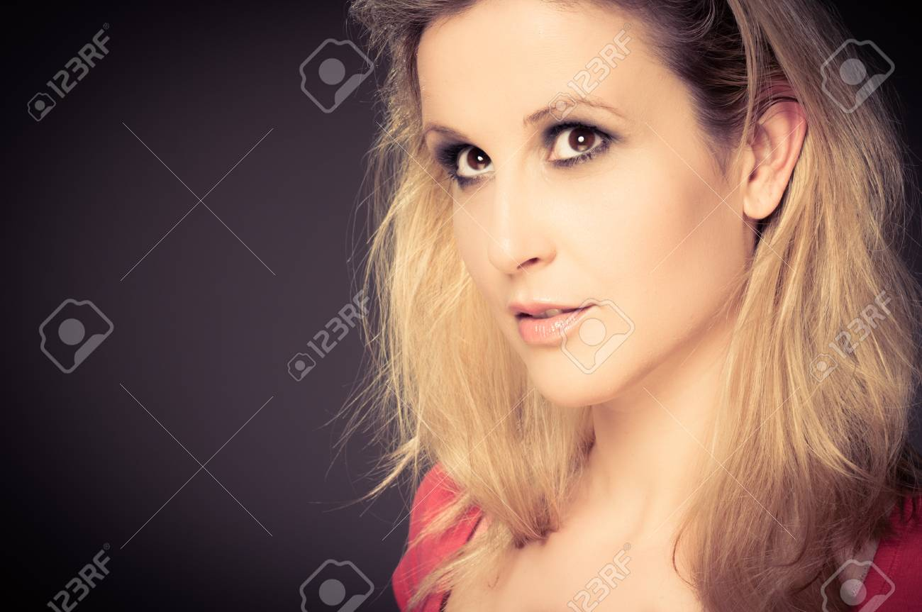 Young adult woman smiling against dark background Stock Photo - 14302237