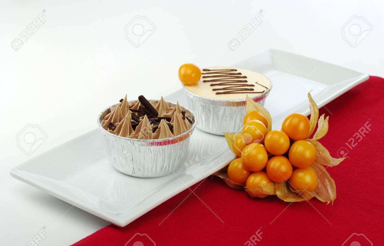 Stock Photo - Two small cakes in tinfoil cups on rectangular white plate with physalis and red table mat (Selective Focus) & Two Small Cakes In Tinfoil Cups On Rectangular White Plate With ...