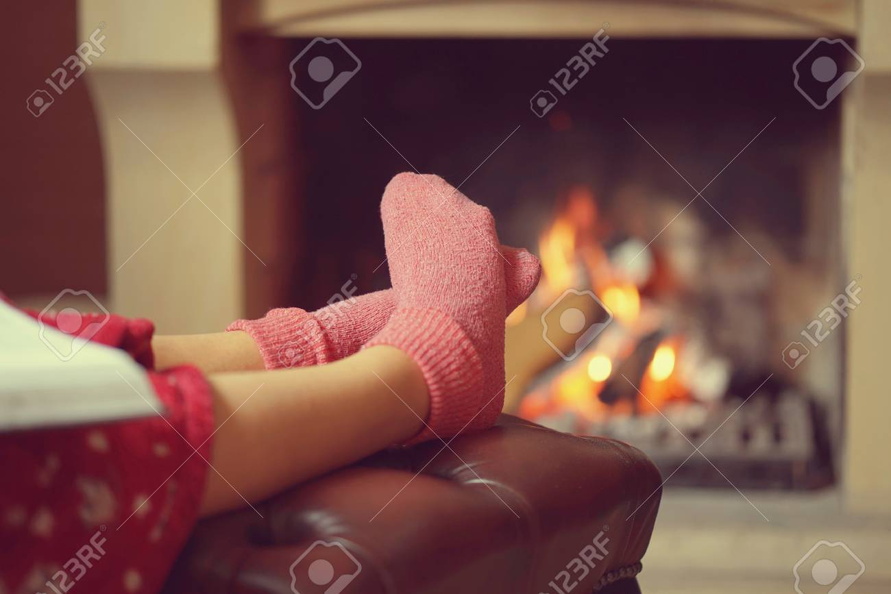 Woman feet with socks sitting near fireplace with a warmth background. Woman in warm socks resting near fireplace at home with book. Toning. - 112157309