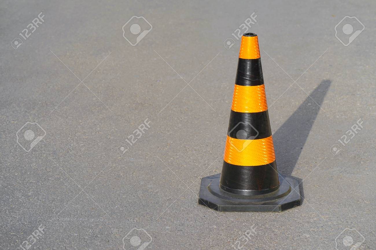 Traffic cone, with black and orange stripes on gray asphalt, copy space. Traffic cone on the road. Road cone on the asphalt. - 124963652